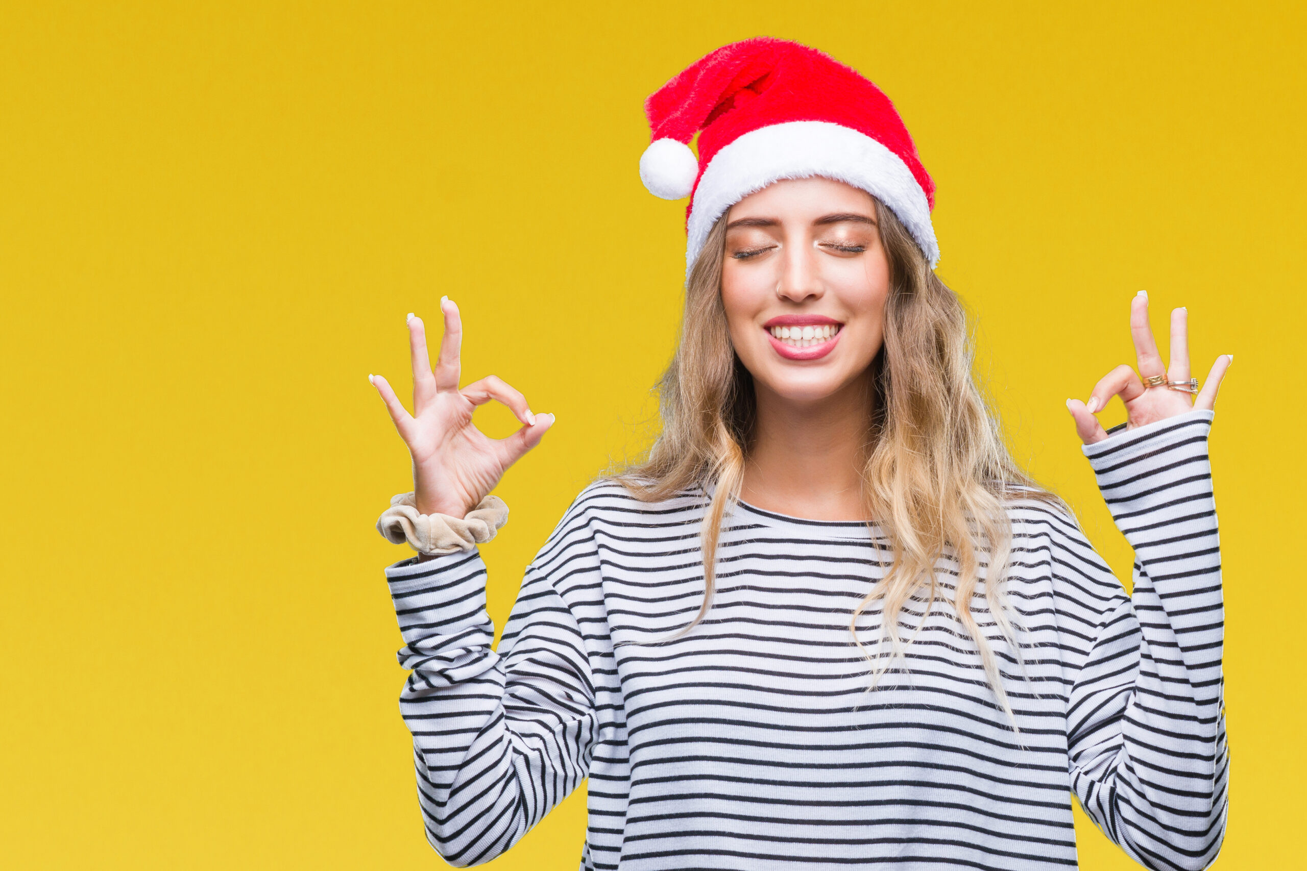 Beautiful young blonde woman wearing christmas hat over isolated background relax and smiling with eyes closed doing meditation gesture with fingers. Yoga concept.